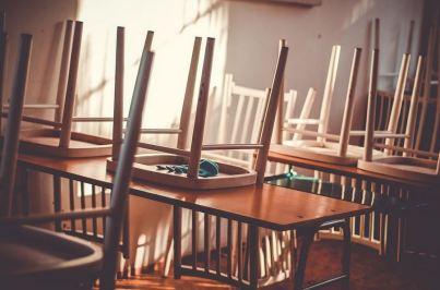 An image of a chairs raised on desks in a classroom.